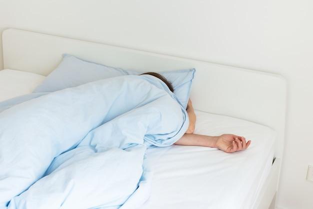 Часть интерьера дома или отеля, женщина спит на белой кровати с синим постельным бельем утром на солнце Premium Фотографии