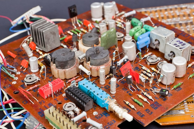 Part of old vintage printed circuit board with electronic components. Premium Photo