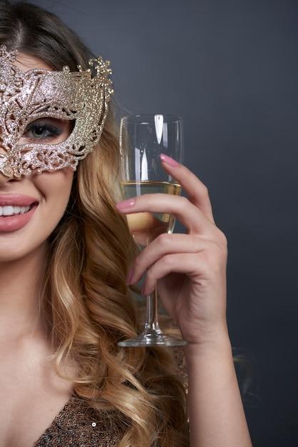 Parte della donna con la maschera che fa un brindisi Foto Gratuite