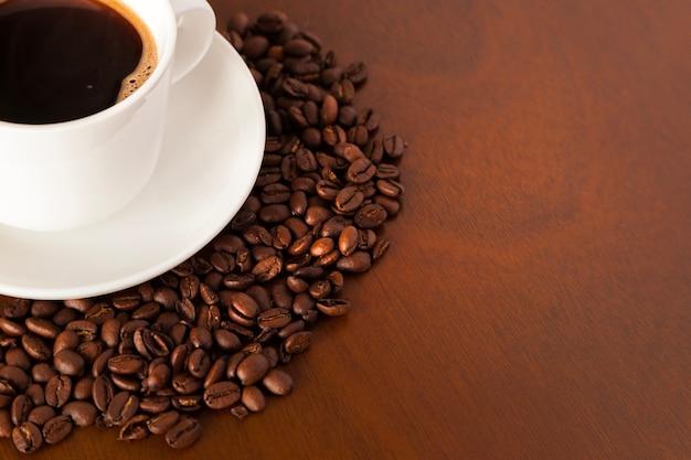 Vista parziale della tazza di caffè e dei fagioli sul tavolo di legno Foto Gratuite