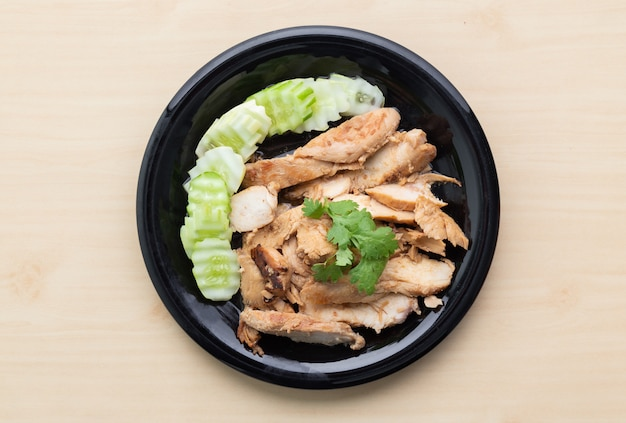 Partially sliced grilled chicken breast with cucumber in black plate on wooden table. Premium Photo