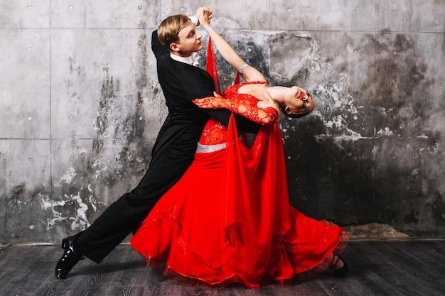 Partners dancing sensual dance near gray wall Free Photo
