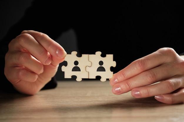 Концепция партнерства из головоломки абстрактных лиц в руках. Premium Фотографии