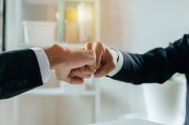 Partnership. two businessman investor hand to fist bumping and joining hands together after complete business deal in meeting room at home office, teamwork cooperate, negotiation and financial concept Premium Photo