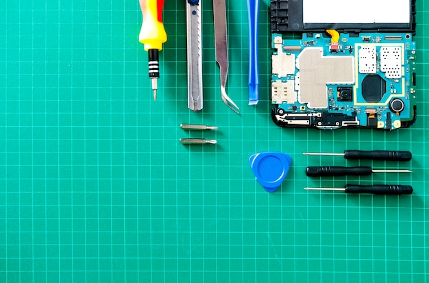 Parts of disassembled gadgets with screw drivers on wooden table Premium Photo