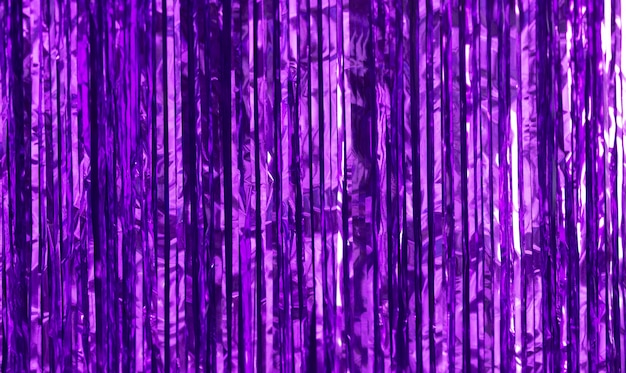 Party background. decor made of purple foil, tinsel and candy. Premium Photo