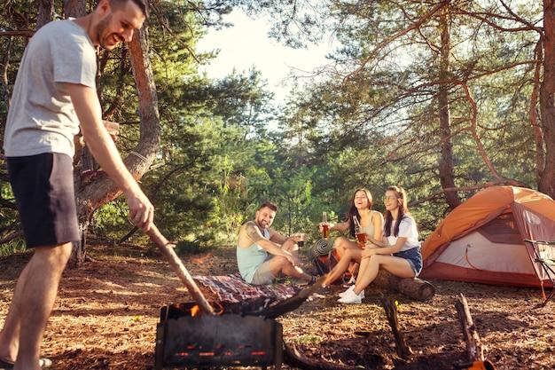 Partito, campeggio del gruppo di uomini e donne nella foresta. vacanza, estate, avventura, stile di vita, concetto di picnic Foto Gratuite