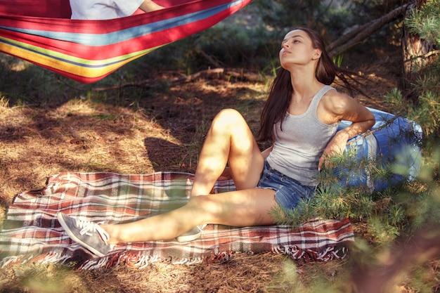 Вечеринка, кемпинг группы мужчин и женщин в лесу. они отдыхают и кушают шашлык Бесплатные Фотографии
