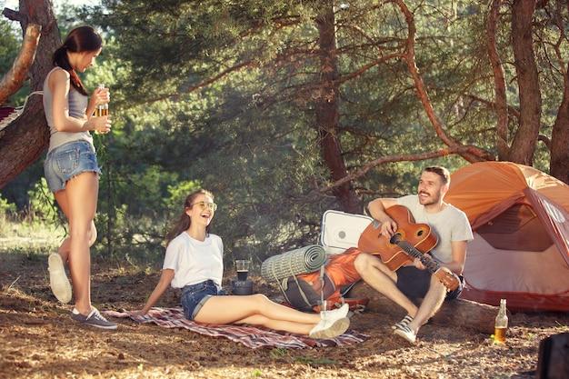 파티, 숲에서 남녀 그룹의 캠핑. 그들은 휴식을 취하고 푸른 잔디를 배경으로 노래를 부릅니다. 휴가, 여름, 모험, 라이프 스타일, 피크닉 개념 무료 사진