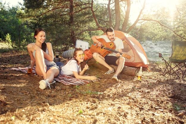 パーティー、森での男女グループのキャンプ。彼らはリラックスし、緑の草に対して歌を歌いました。休暇、夏、冒険、ライフスタイル、ピクニックの概念 無料写真