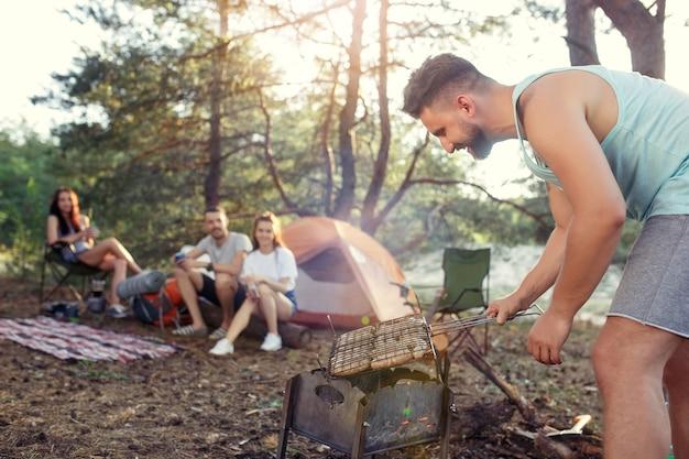 파티, 숲에서 남녀 그룹의 캠핑. 그들은 휴식을 취하고 노래를 부르며 푸른 잔디에 대해 바베큐 요리를합니다. 휴가, 여름, 모험, 라이프 스타일, 피크닉 개념 무료 사진