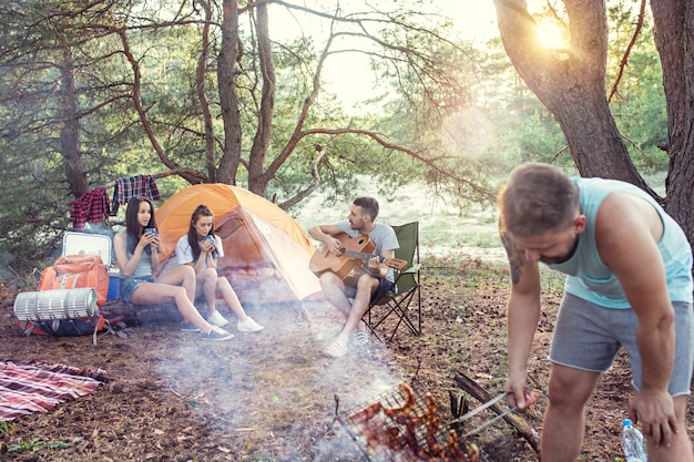 숲에서 남녀 그룹의 파티, 캠핑 무료 사진