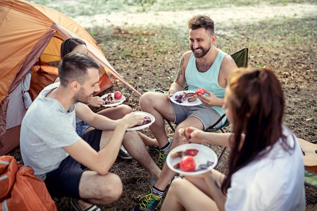Вечеринка, кемпинг мужской и женской группы в лесу Бесплатные Фотографии