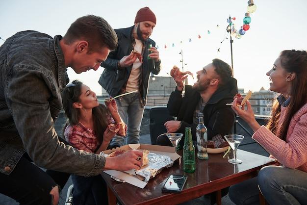 Партийная концепция. едят пиццу на вечеринке на крыше. у хороших друзей выходные с вкусной едой и алкоголем Бесплатные Фотографии