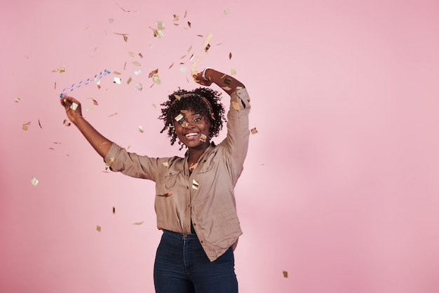 パーティーの構想。紙吹雪を宙に投げる。背後にあるピンクの背景を持つアフリカ系アメリカ人の女性 無料写真