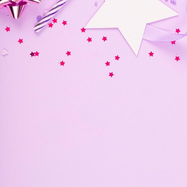 리본, 별, 생일 촛불, 분홍색 표면에 색종이와 파티 휴일 표면 프리미엄 사진