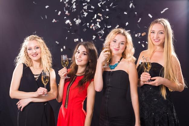 Концепция партии, праздников, празднования и ночной жизни - улыбающиеся подруги с бокалами шампанского в клубе. Premium Фотографии