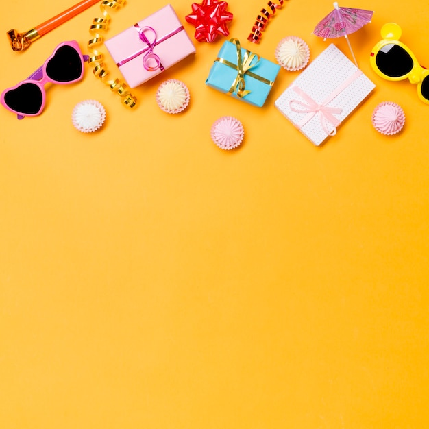 Party horn; sunglasses; streamers; wrapped gift boxes; and aalaw on yellow backdrop Free Photo