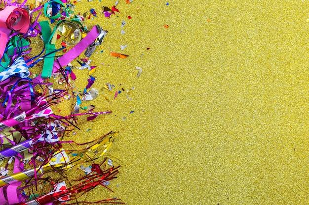 Party horns on shiny confetti Free Photo