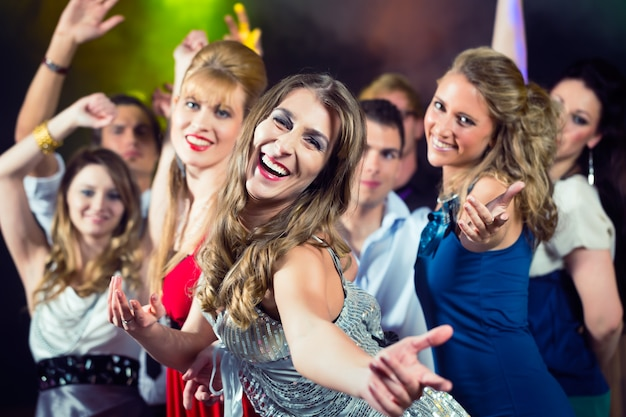 Party people dancing in disco club Premium Photo