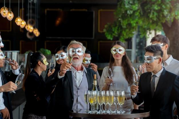 파티 사람들은 술을 마시고 축하하기 위해 와인 잔을 집어 드는 임원 비즈니스 팀의 멋진 마스크입니다. 프리미엄 사진
