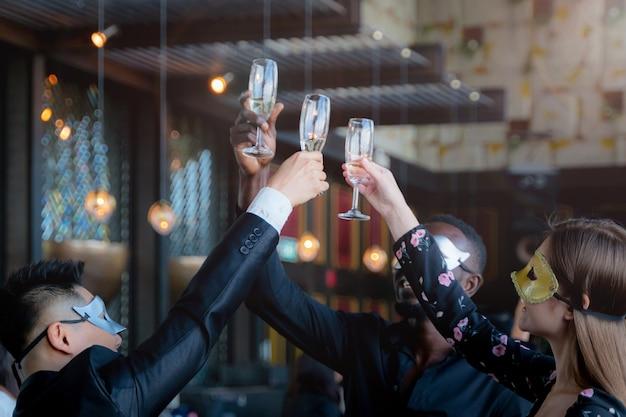 파티 사람들은 술과 이야기를 위해 와인 잔을 따기 임원 비즈니스 팀의 멋진 마스크. 프리미엄 사진