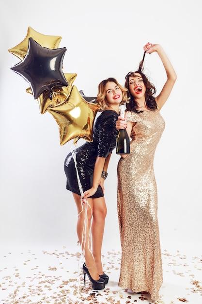 칵테일 우아한 드레스 포즈에서 두 가장 친한 친구의 파티 시간. 반짝이는 황금 색종이. 물결 모양의 헤어 스타일. 파티 풍선. 무료 사진