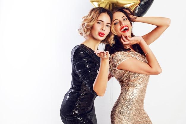 エレガントなカクテルドレスのポージングで2人の親友のパーティータイム。きらめく金色の紙吹雪。ウェーブのかかった髪型。パーティー風船。 無料写真