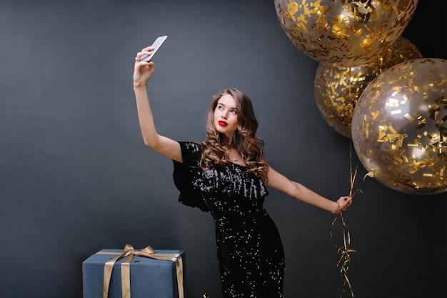 黒の豪華なドレスを着た若い魅力的な女性のパーティータイム。長い巻き毛のブルネットの髪が、金色のティンセルでいっぱいの大きな風船で自分撮りをします。プレゼント、お祝い、モダン。 無料写真