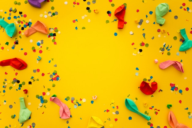 Party with confetti remnants and colorful balloons on yellow Free Photo