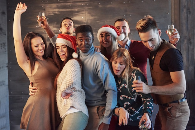 Party with friends. they love christmas. group of cheerful young people carrying sparklers and champagne flutes dancing in new year party and looking happy. concepts about togetherness lifestyle Premium Photo