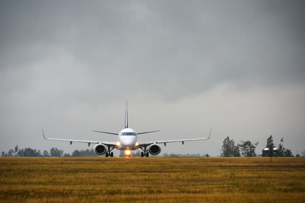 Passenger aircraft with lights on will travel to runway in the airport field in the evening in the rain Premium Photo