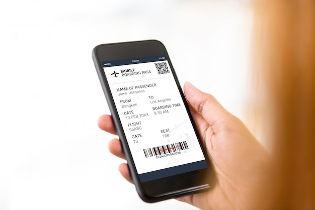 Passenger looking at electronic boarding pass on smartphone screen Premium Photo