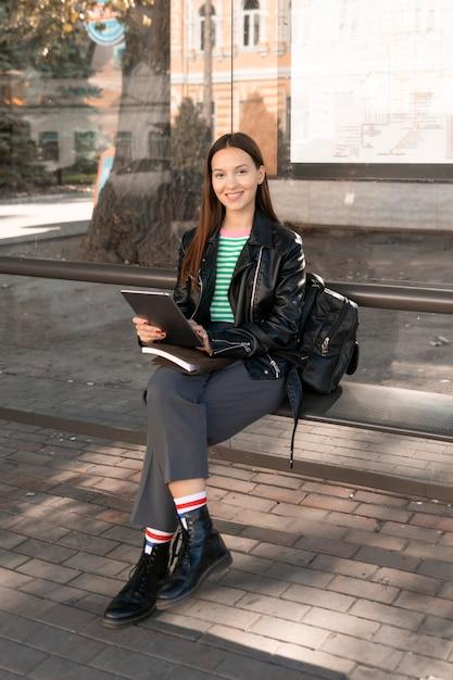 Passeggero seduto su una panchina della stazione lungo tiro Foto Gratuite