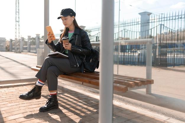 Passeggero seduto su una panchina della stazione e utilizzando il telefono cellulare Foto Gratuite