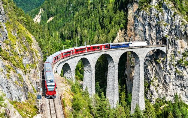 Passenger train crossing the landwasser viaduct in the swiss alps Premium Photo