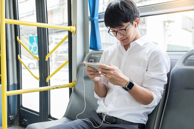 Premium Photo | Passenger transport. people in the bus, listening music and play game while riding home.
