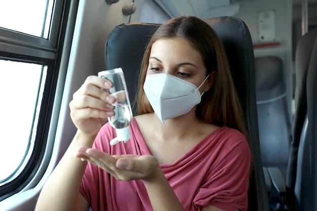 Пассажир в защитной маске дезинфицирует руки в общественном транспорте Premium Фотографии
