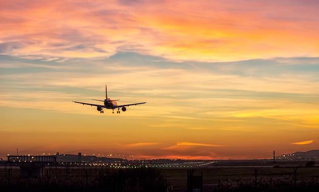 Passengers airplane landing to airport runway in beautiful sunset light Premium Photo