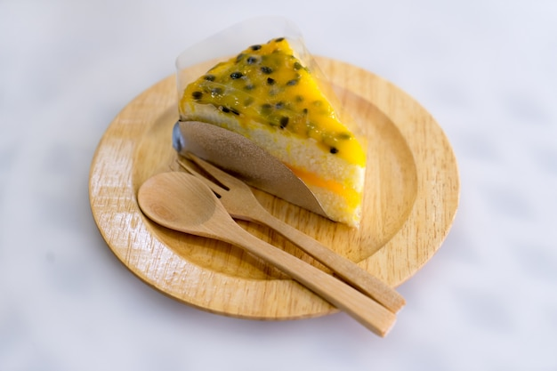 Passion fruit cake on wood plate Premium Photo