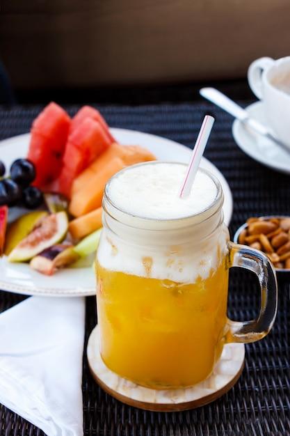 Страстный пунш коктейль. освежающий напиток из тропического коктейля из маракуйи в стеклянной банке. орехи, арахис, капучино и фрукты. Premium Фотографии