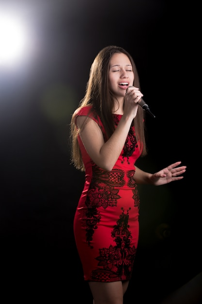 Passionate singer in red dress Free Photo