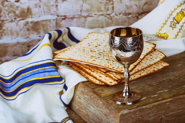 Passover background red wine and matzoh jewish holiday bread over wooden board . Premium Photo