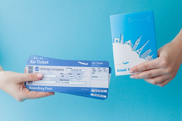 Passport and air ticket in woman hand on a blue background. travel concept, copy space Premium Photo