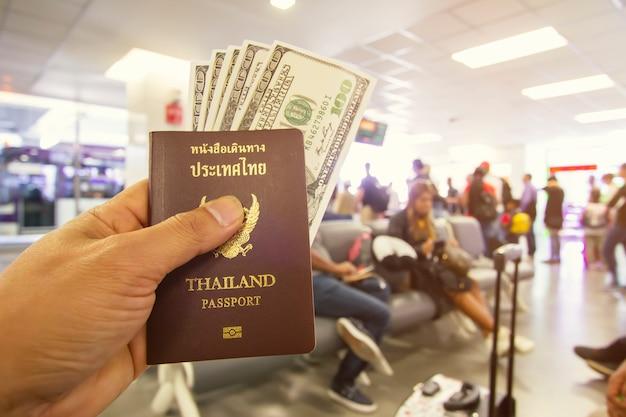 パスポートと空港に座っている男性の手でドル Premium写真