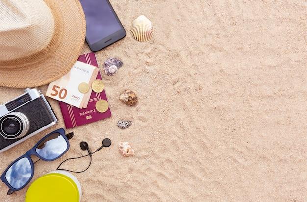 パスポートと現金、スマートフォン、帽子、カメラ、サングラスを砂の上に。フラットレイ Premium写真
