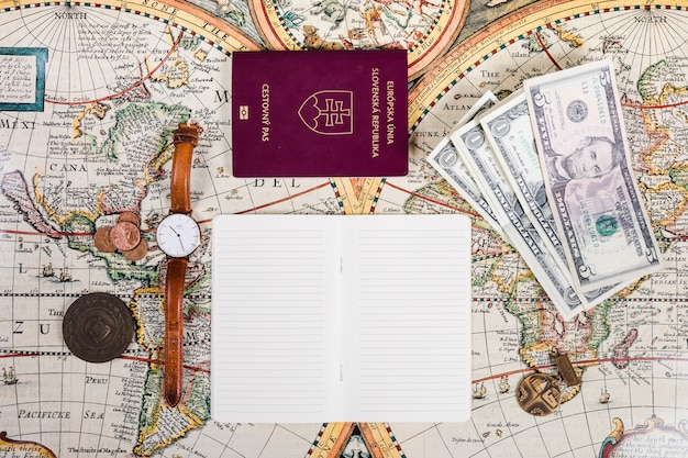 Passport, banknotes, wristwatch, coins and notepad on map Free Photo