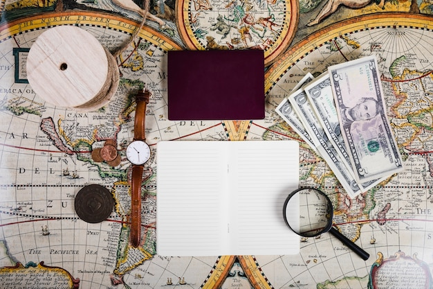 Passport and diary with antique equipments on world map Free Photo