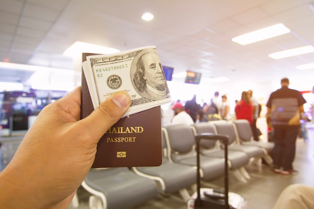 Passport and dollar in male hands sitting in the airport Premium Photo