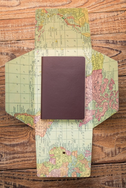 Passport on top of a world map seen from above Free Photo